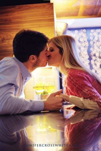 couple kissing over the table.