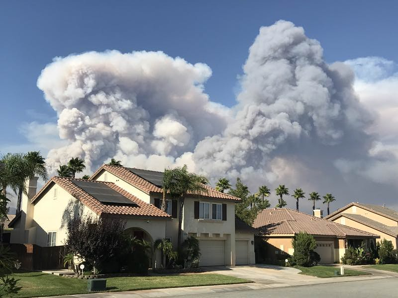 Smoke from the 2020 California Apple Fire behind houses.
